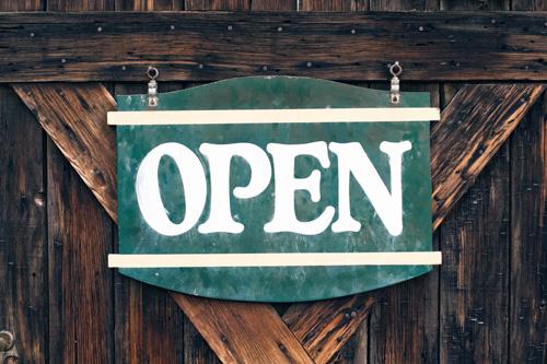 Rustic open sign hanging on wooden door